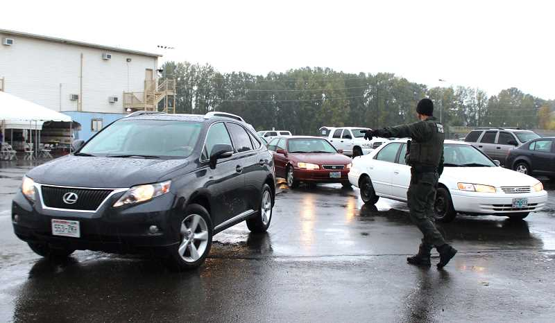 REVIEW PHOTO: SAM STITES - Dozens of teen drivers are directed to the start of an obstacle course created by the Clackamas County Sheriff's Office to test their basic skills and techniques.