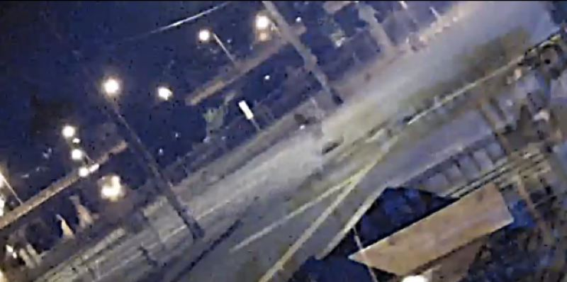 A security camera video shows the fatal collision that ended the life of Portland artist Tamar Monhait. This still shows her in the intersection of Southeast Water Avenue and Taylor Street shortly before a garbage truck owned by McInnis Waste Systems, Inc. appears in view, colliding with her.