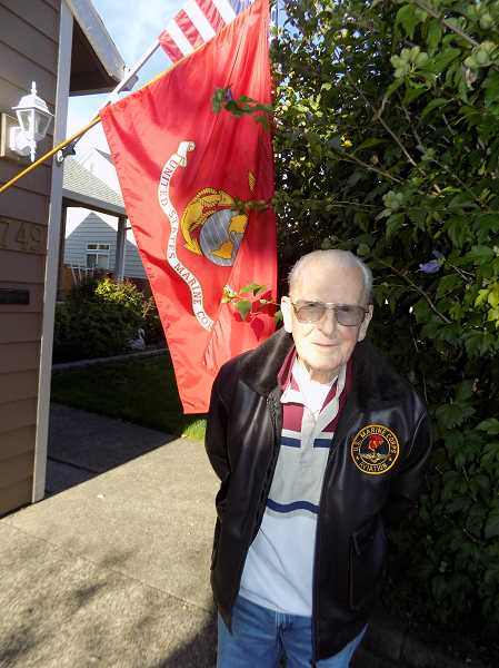 GAZETTE PHOTO: RAY PITZ - World War II and Korean War veteran Rick Lowry stands next to the American flag and a U.S. Marine Corps flag.
