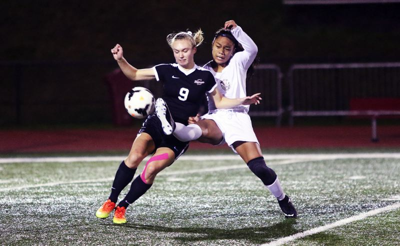 DAN BROOD - Sherwood junior Jenna Funk (left) and Tualatin freshman Cally Togiai battle for the ball in last week's match.