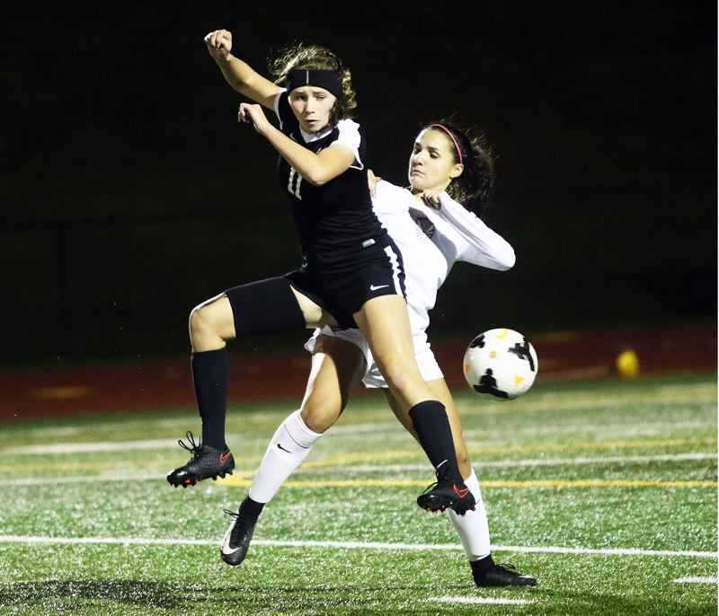 DAN BROOD - Sherwood junior Mia Stallard (11) knocks the ball away during the match at Tualatin.