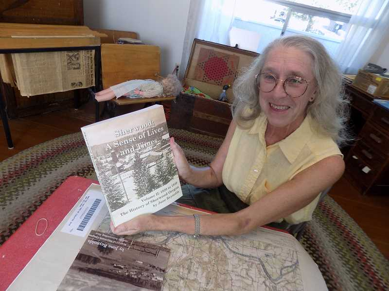 GAZETTE PHOTO: RAY PITZ - June Reynolds displays her new book, Sherwood: A Sense of Lives and Times, Volume II: 1920 to 1939, The History of Sherwood, Oregon, during an interview at the Morback House, headquarters of the Sherwood Historical Society.