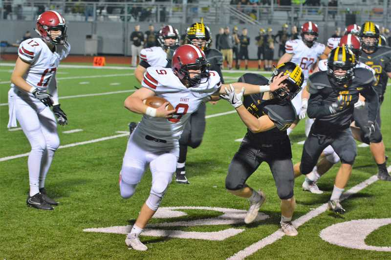 SPOTLIGHT PHOTO: JAKE MCNEAL - Sandy sophomore running back Colby Carson stiff-arms St. Helens junior defensive back Cade Duarte.