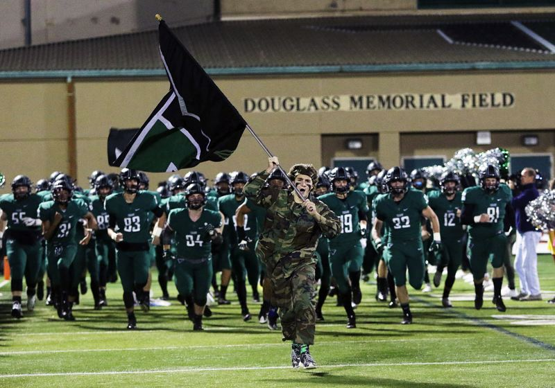 DAN BROOD - The Tigard High School football team takes the field, at Tigard, prior to the start of Friday's game.