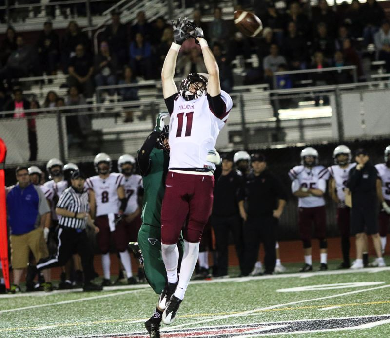 DAN BROOD - A pass is just out of the reach of leaping Tualatin senior receiver Nick Savage.