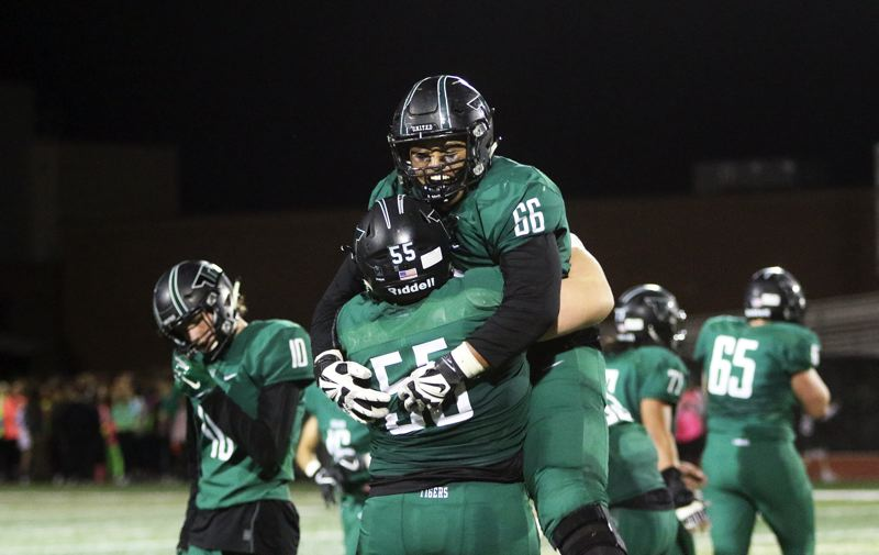 DAN BROOD - Tigard linemen Laytan Tanuvasa (66) and Sean Ryan celebrate following the end of Friday's game.