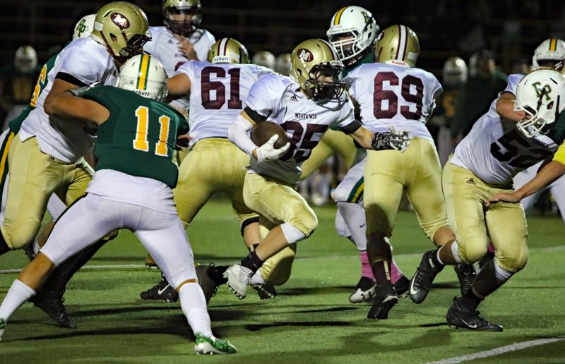 REVIEW/NEWS PHOTO: JIM BESEDA - Milwaukie's Cameron McPherson finds running room during the second half of Friday's Northwest Oregon Conference game at Putnam.