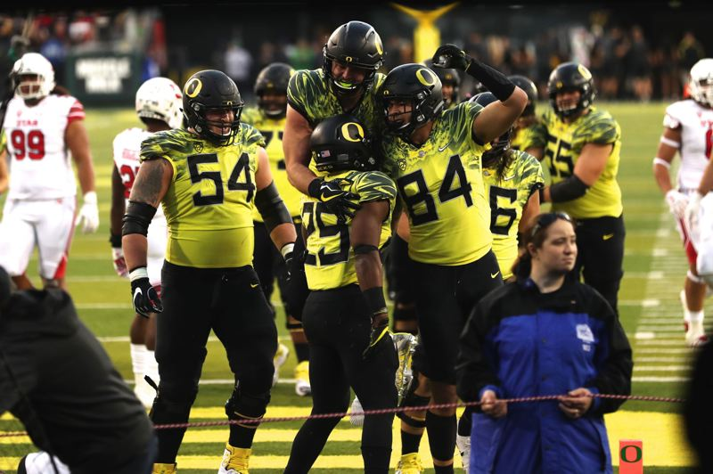 TRIBUNE PHOTO: JAIME VALDEZ - Oregon teammates celebrate with running back Kani Benoit after his late touchdown against Utah.