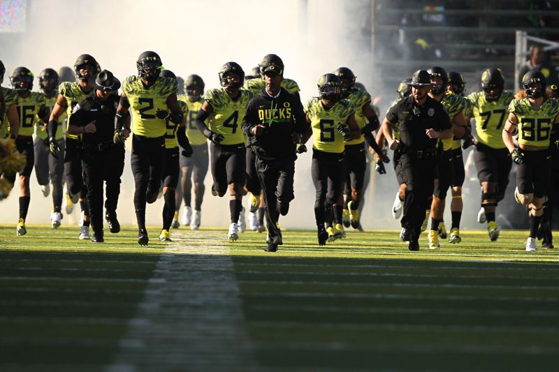 TRIBUNE PHOTO: JAIME VALDEZ - Coach Willie Taggart and the Oregon Ducks take the field for Saturday's game.