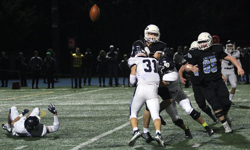 REVIEW PHOTO: MILES VANCE - The Lake Oswego defense puts a hit on Lakeridge receiver Will Scadden during the Lakers' 35-6 win on Friday night at Lakeridge High School.