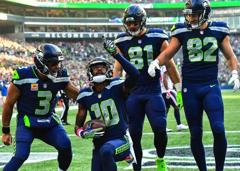MICHAEL WORKMAN PHOTO - From left, Seattle quarterback Russell Wilson celebrates a touchdown with receiver Paul Richardson and teammates Nick Vannett and Luke Wilson.