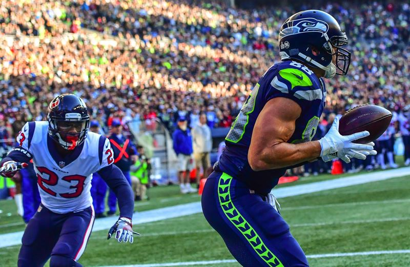 MICHAEL WORKMAN PHOTO - Jimmy Graham (right) hauls in a Russell Wilson pass against Houston's Kurtis Drummond.