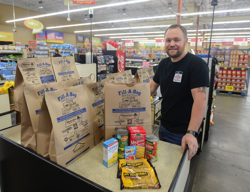OUTLOOK PHOTO: JOSH KULLA  - Grocery Outlet owner Cory Price says it's a no-brainer to help the community. His store is offering $5 bags of groceries for shoppers to purchase and donate now through Jan. 5, 2018.