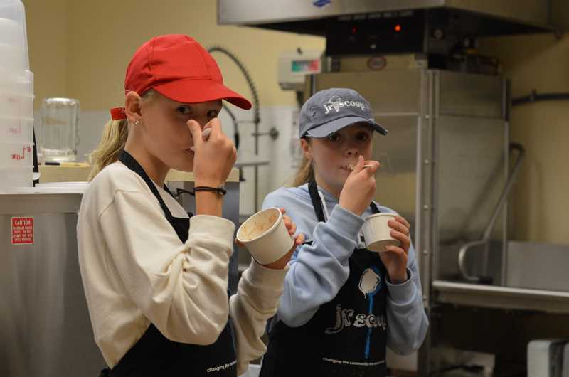 SPOKESMAN PHOTO: CLARA HOWELL - Sixth-grader Olivia Lyons (left) and seventh-grader Mia Combs (right) taste leftover ice cream they made.