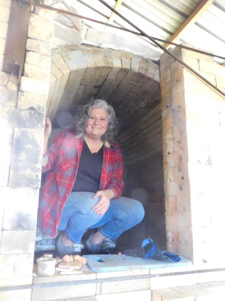 ESTACADA NEWS PHOTO: EMILY LINDSTRAND - Brenda Scott smiles from inside of the kiln in which she creates her pottery, located in her backyard. Scotts upcoming show at The Spiral Gallery features both pottery and collages.