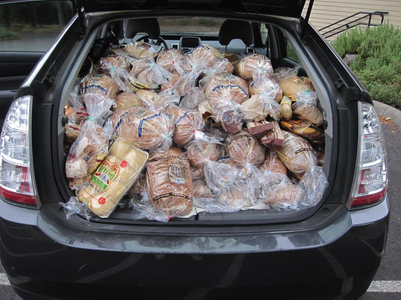 COURTESY: SUSIE SNORTUM - A load of donated bread from Bales Thriftway in Beaverton gets packed into a volunteer's van for distribution to those who need it.