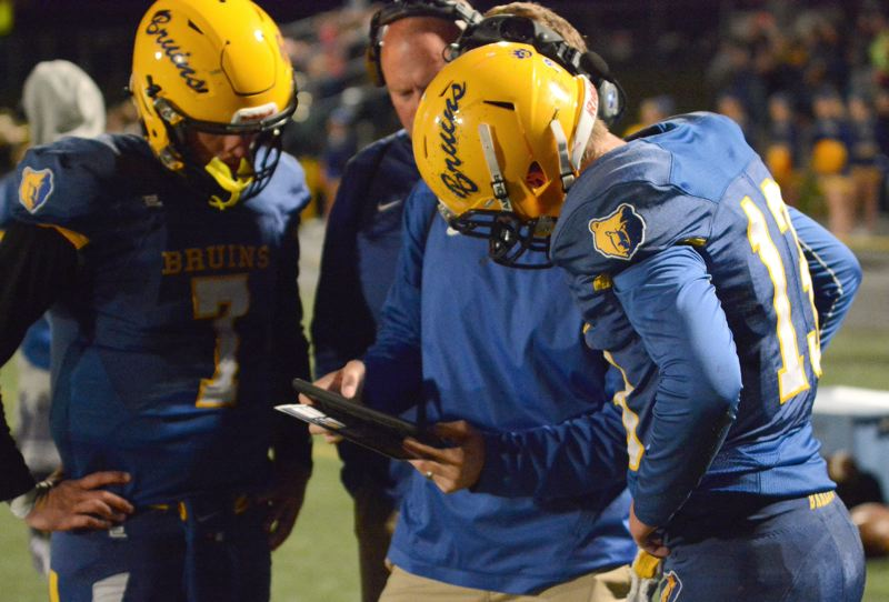 OUTLOOK PHOTO: DAVID BALL - Austin Davis and Jaren Hunter go over the play list along the sideline with quarterback coach Alex Grandjean and Bruins head coach Terry Summerfield.