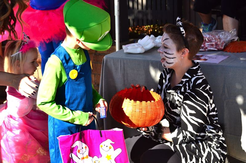 POST PHOTO: BRITTANY ALLEN - Clackamas County Bank did not disappoint at the Trick or Treat Trail. Several staff members showed up in costume to hand out sweet treats on the street.