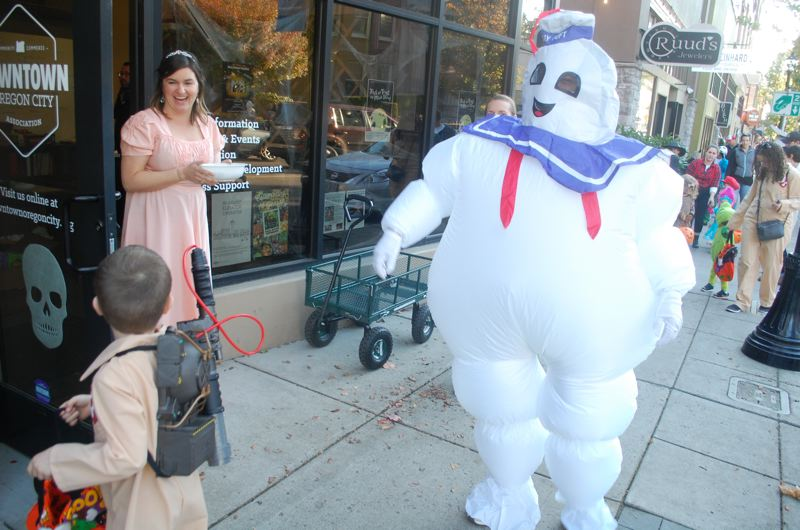 PHOTO BY: RAYMOND RENDLEMAN - Tyson Lowther, as the Stay Puft Marshmallow Man from 'Ghostbusters,' walks Oregon City Main Street with his wife, Jennifer, and their sons Owen, 6, and Logan, 2.