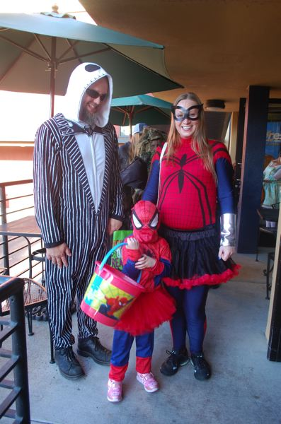 PHOTO BY: RAYMOND RENDLEMAN - Joshua and Jenny Edwards dress as action figures to trick-or-treat at Coffee Rush with their daughter, Zara, 4.