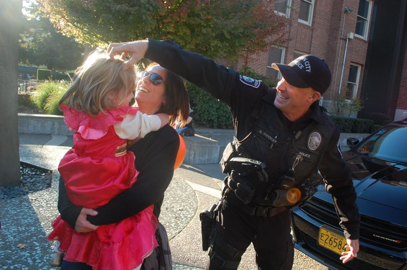 PHOTO BY: RAYMOND RENDLEMAN - Wendy Libke and her daughter Ziva enjoy the Trick or Treat on Main Street celebration with Oregon City Police Officer Dan Shockley.