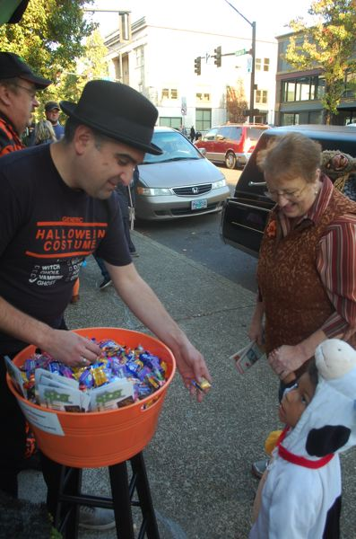 PHOTO BY: RAYMOND RENDLEMAN - Former Oregon City Commissioner Rocky Smith hands out candy at the Trick or Treat on Main Street celebration on Oct. 31.