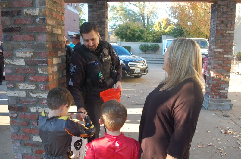 PHOTO BY: RAYMOND RENDLEMAN - Oregon City Police Officer Dave Edwins hands out candy at the Trick or Treat on Main Street celebration.