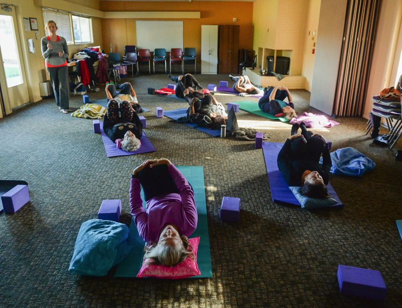 OUTLOOK PHOTO: JOSH KULLA - Patti Stone (standing) yoga instructor, gently talks people affected by cancer through easy yoga poses and breathing at a free class at Legacy Mount Hood Medical Center.
