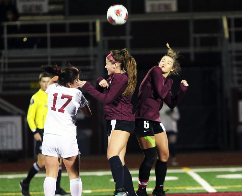 DAN BROOD - Tualatin senior Rachael Breyer (right) and junior Skylar Maddox battle Sherwood junior Gillian Pedan for the ball during Tuesday's Class 6A girls soccer second-round state playoff match. The Wolves won 4-2.