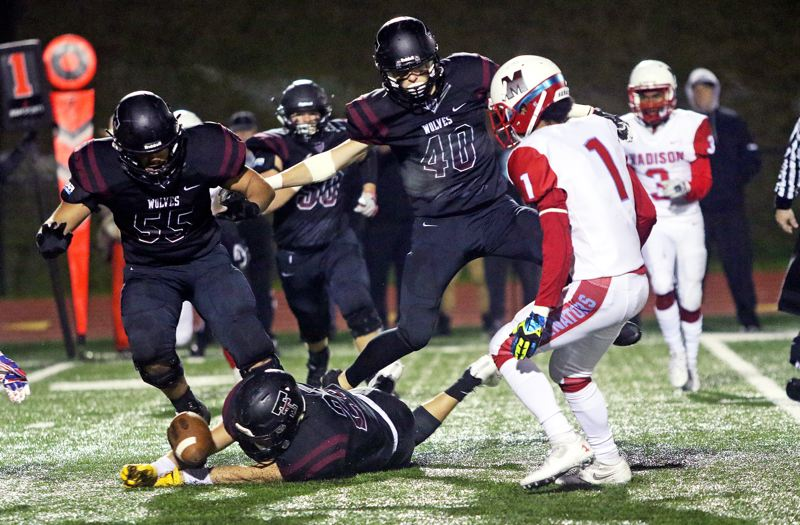 DAN BROOD - Tualatin senior Ivan Garibay dives for the ball on a Madison fumble, while Timberwolf senior Jarius Jackson (55) and junior Jalen Hale also close in.