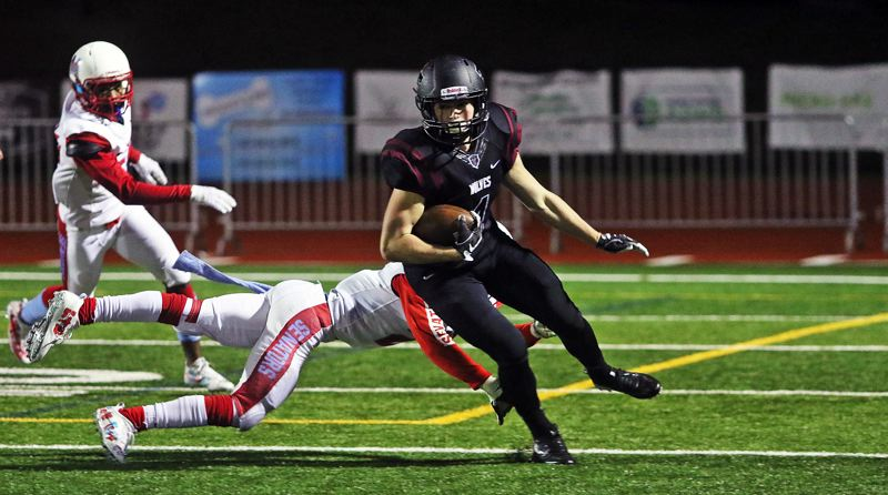 DAN BROOD - Tualatin senior Nathan Marx turns up field after getting past a Madison defender in Friday's state playoff game.