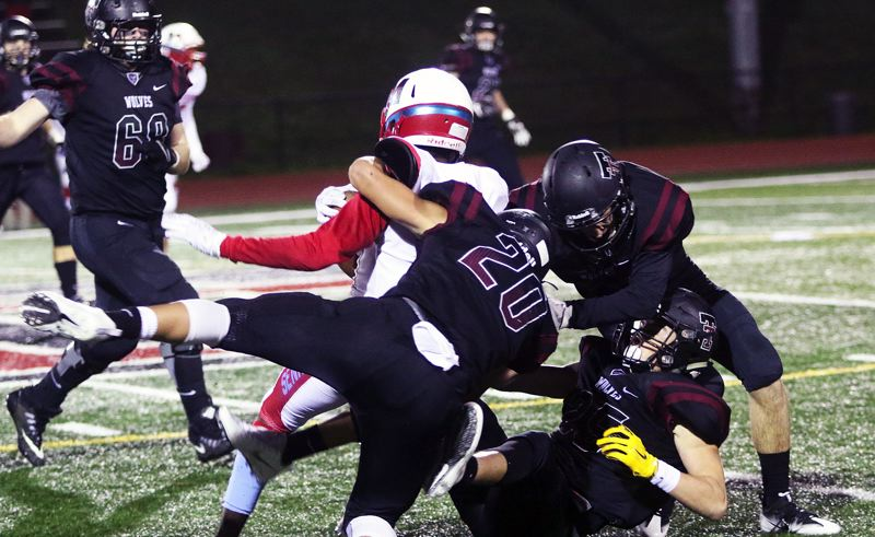 DAN BROOD - Tualatin's John Miller, Ivan Garaby and Colby Jackson bring down Madison junior Trey Ratcliff.