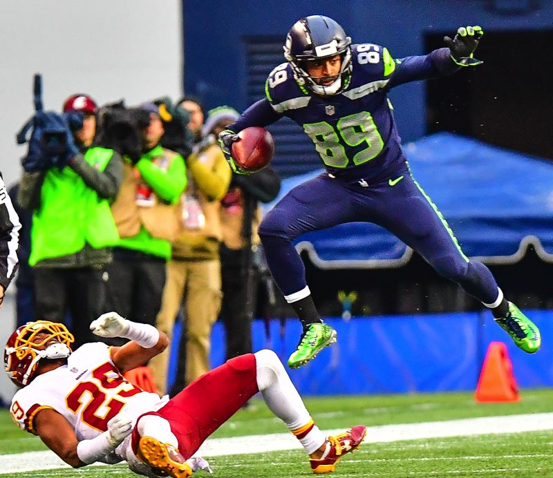 MICHAEL WORKMAN PHOTO - Seattle's Doug Baldwin leaps over Kendall Fuller of Washington.