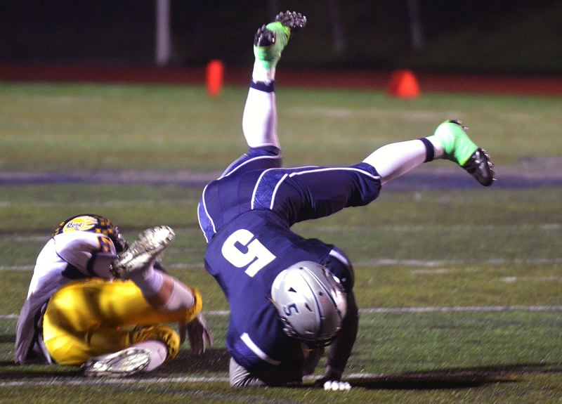 SPOKESMAN PHOTO: TANNER RUSS - Wilsonville running back Cooper Mootz tumbles over a Bend tackler during the Wildcats' 42-21 home win in the first round of the Class 5A state playoffs on Friday.