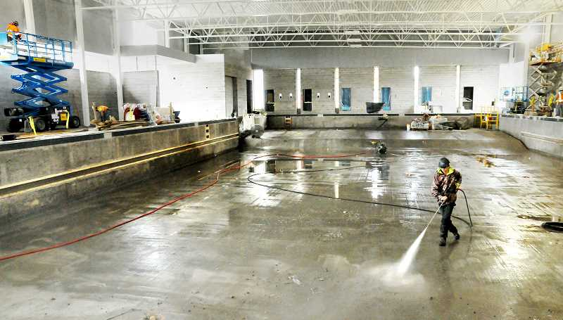GARY ALLEN - A worker prepares the surface of the competition pool for sealing and painting last week.