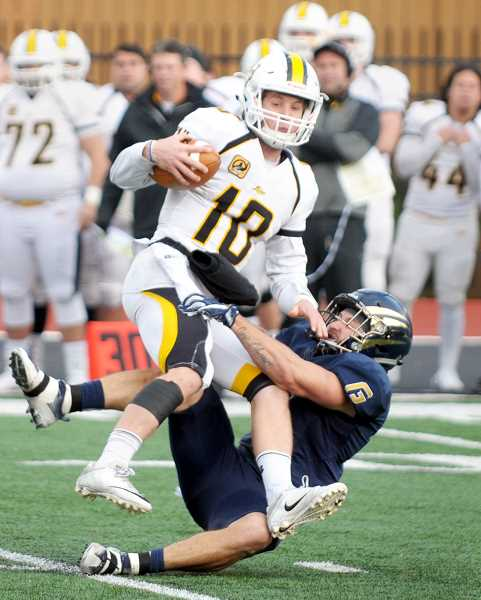 SETH GORDON - George Fox senior Ryan Russo drags down Pacific Lutheran quarterback Walker LaVoy to force a turnover on downs late in the Bruins 13-3 home loss to the Lutes.