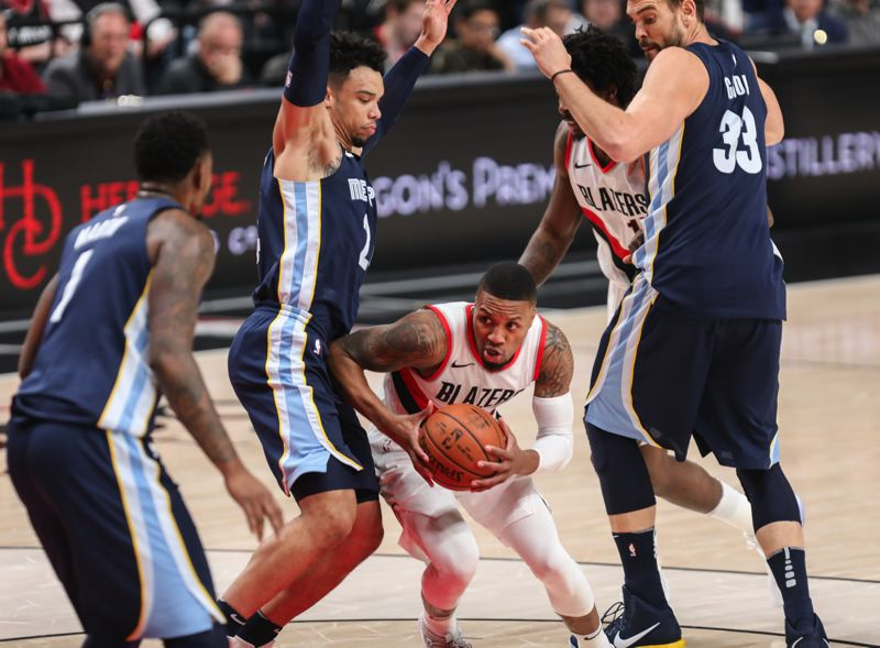 TRIBUNE PHOTO: DAVID BLAIR - Blazers guard Damian Lillard squeezes between Memphis defenders (from left) Jarell Martin, Dillon Brooks and Marc Gasol.