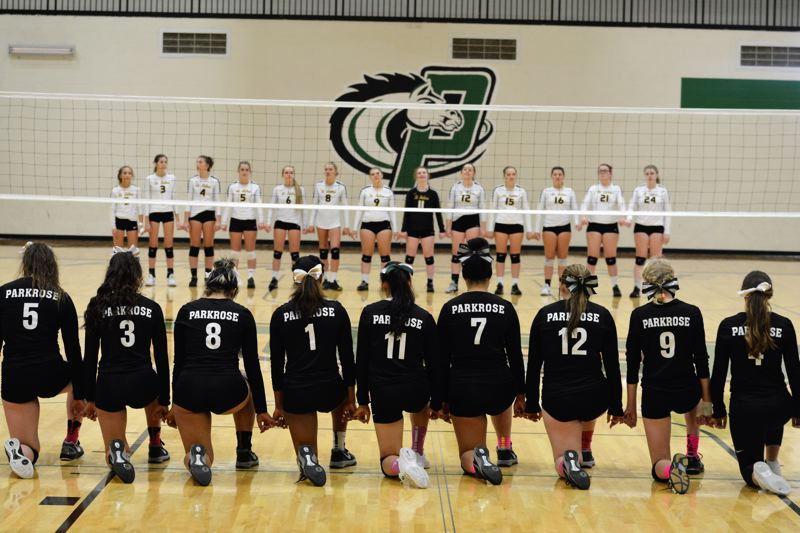 TRIBUNE PHOTO: JAKE MCNEAL - Parkrose High Schools varsity girls volleyball team knelt Oct. 2 during the national anthem before the game against St. Helens High School.