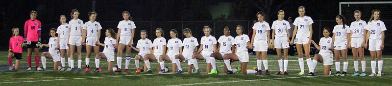 TRIBUNE PHOTO: MILES VANCE - A portion of the Grant High School girls soccer team knelt during the national anthem before the Oct. 31 playoff game against Lake Oswego High School.