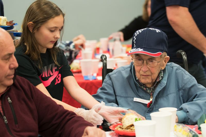 TIMES PHOTO: JAIME VALDEZ - Myla Wilson, 9, serves breakfast to World War II Army veteran Lee Driscoll, 102, during a breakfast for veterans at the Juanita Pohl Center on Thursday.