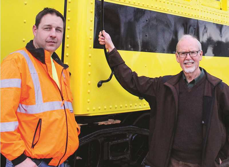 JASON CHANEY - Railway General Manager Matt Wiederholt (left) and Bowman Museum Director Gordon Gillespie pose for a photo in front of the caboose at its new location.