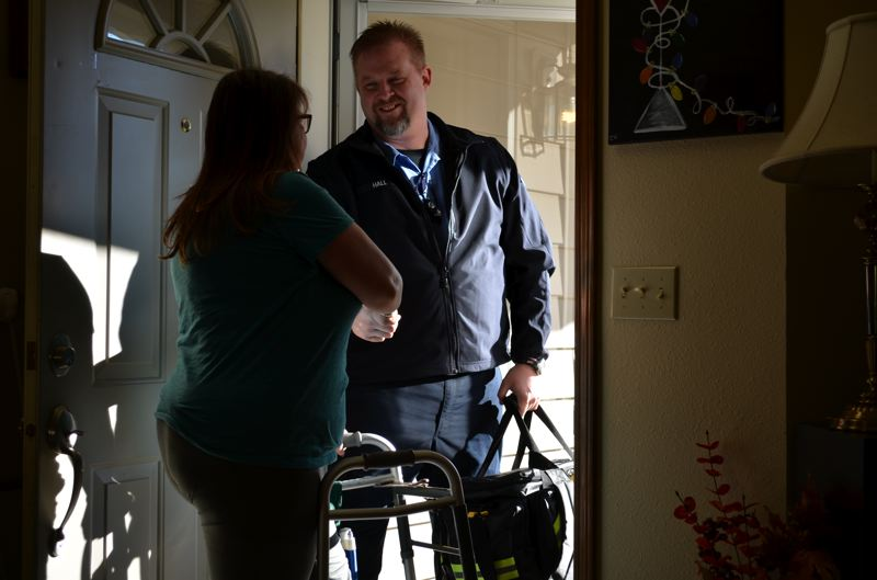 PHOTO COURTESY: CLACKAMAS FIRE - American Medical Response Community Paramedic Dan Hall talks with a patient who is using a walker to get arong her home.