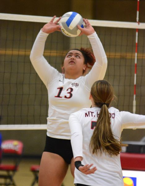 OUTLOOK PHOTO: DAVID BALL - Mt. Hood setter Elisha Levasa puts a ball up at the net, while teammate Shelby Martin prepares to go on the attack during the Saints four-set loss to Clark College on Wednesday.