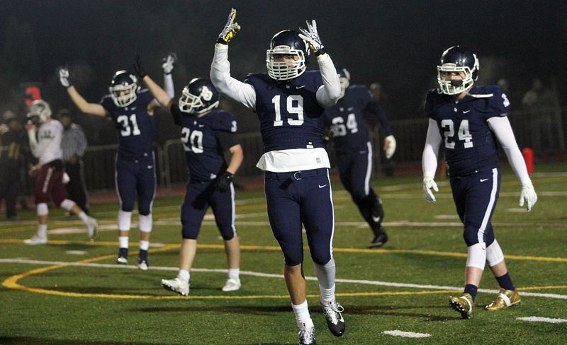 REVIEW PHOTO: MILES VANCE - Lake Oswego's Marshall McGuire leads his team in cheers at the end of the third quarter of its 45-0 win over Sherwood in the second round of the Class 6A state playoffs on Friday at Lake Oswego High School.