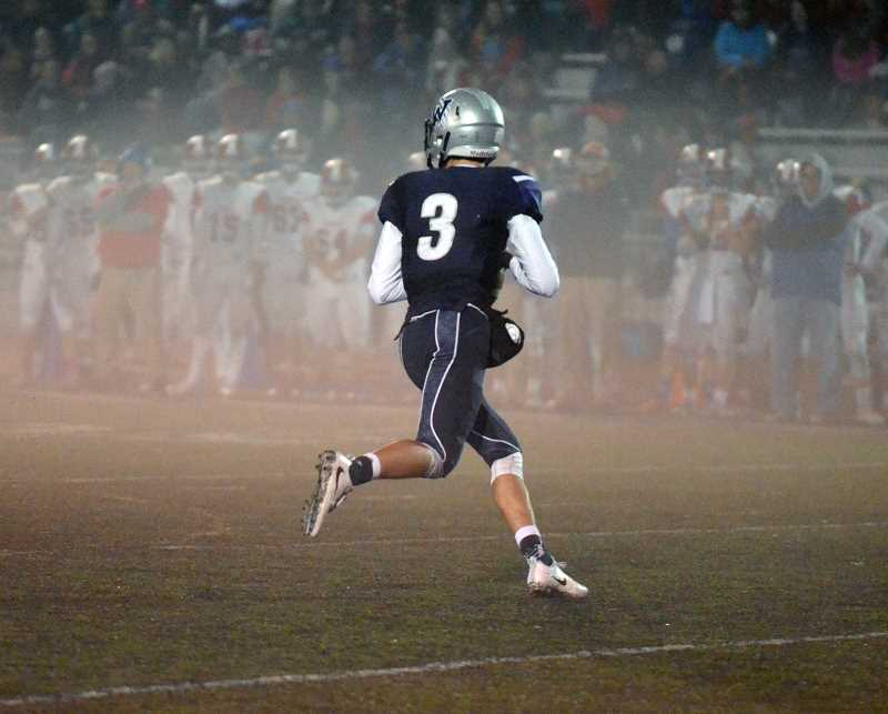 SPOKESMAN PHOTO: TANNER RUSS - Overholt scrambles out of the pocket in the fog. Overholt ran for one touchdown, and passed for two more on Nov. 10.