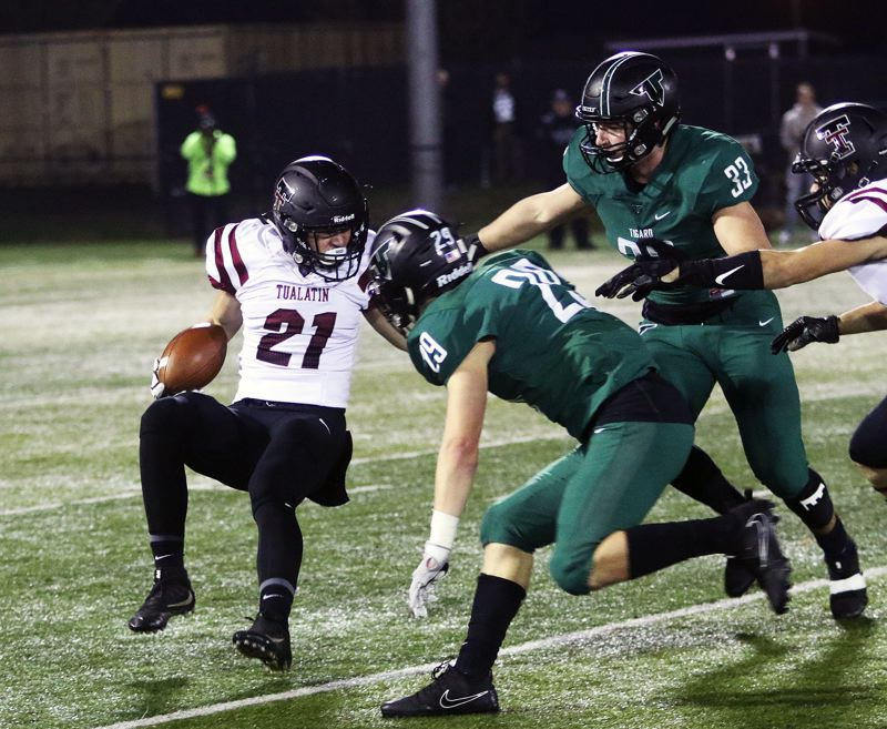DAN BROOD  - Tigard seniors Spencer Smith (29) and Kyle Bay close in on Tualatin sophomore running back Kainoa Sayre.