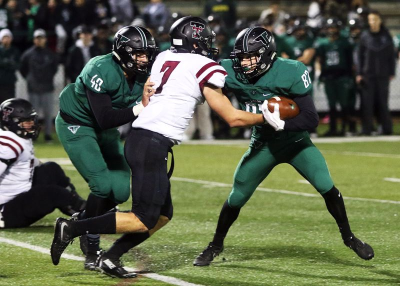 DAN BROOD - Tualatin senior Lucas Noland (7) brings Tigard sophomore Hunter Gilbert down for a loss during Friday's playoff game.