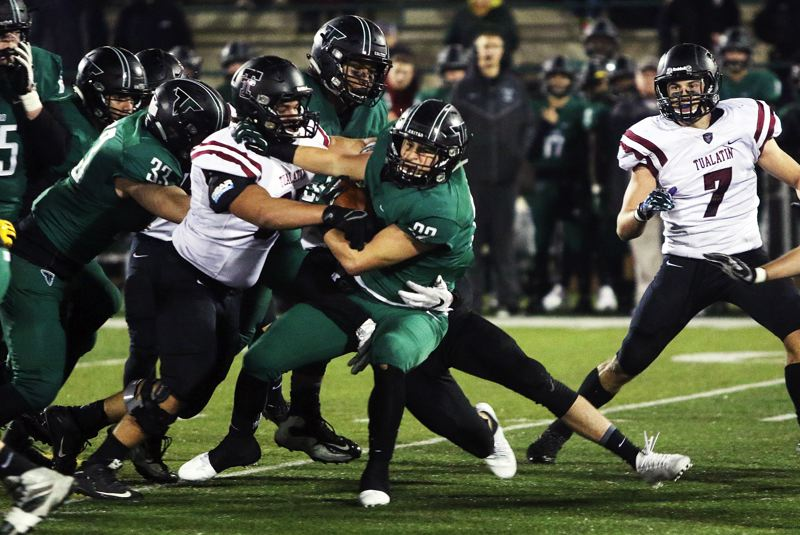 DAN BROOD - Tigard senior running back Jake Leavitt powers his way for more yardage during Friday's playoff game.