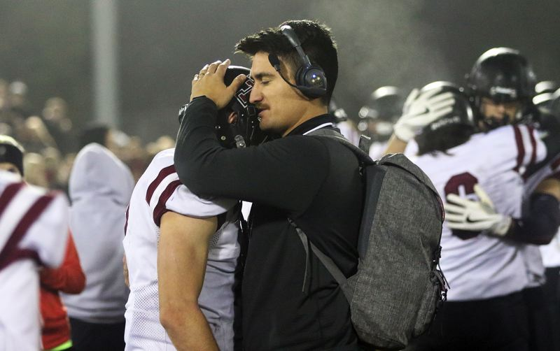 DAN BROOD - Tualatin assistant coach Woody Toms hugs Timberwolf senior Lucas Noland toward the end of Friday's playoff game at Tigard.