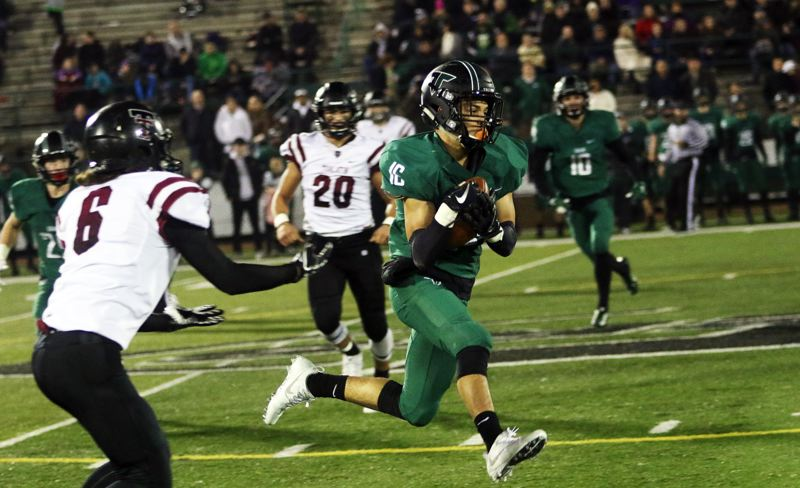 TIMES PHOTO: DAN BROOD - Tigard sophomore Max Lenzy races through the Tualatin defense after making an interception and returning it 51 yards for a touchdown during the Tigers' 38-17 home win in the second round of the Class 6A state playoffs on Friday.